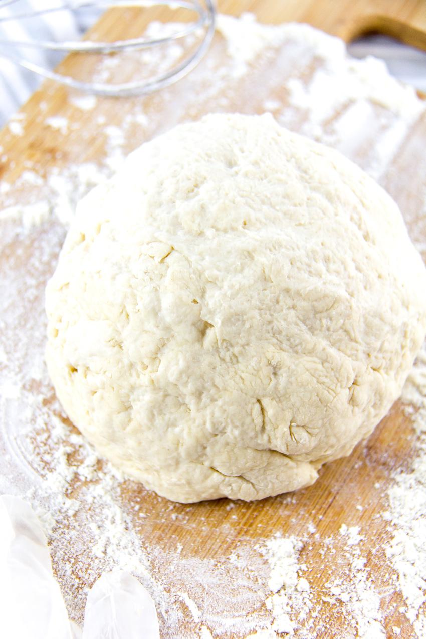 a ball of dough on a floured cutting board