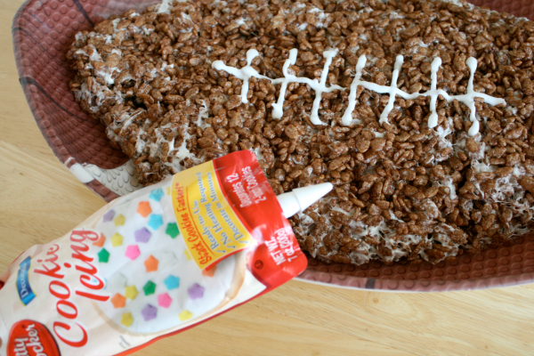 Add Frosting to a Giant Rice Crispy Football for the White String