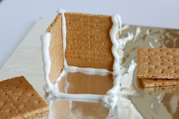Adding frosting to graham crackers for candy houses