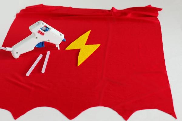 Gluing on the lightning bolt for a superhero kids cape