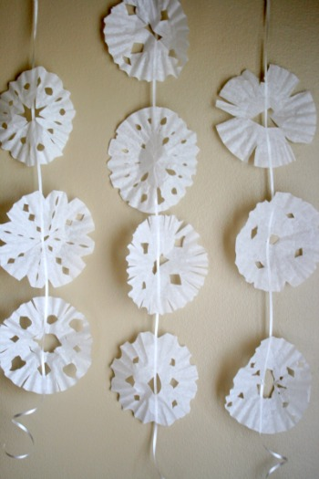 To hang these on a string, tape ribbon or yarn to the back of the snowflake. Line up down the string with about 4 feet of ribbon. Now hang these snowflakes on your wall or window to create a snowy scene!