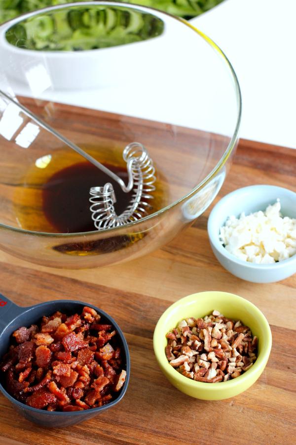 Mixing Arugula Salad with Bacon, Feta, and Pecans