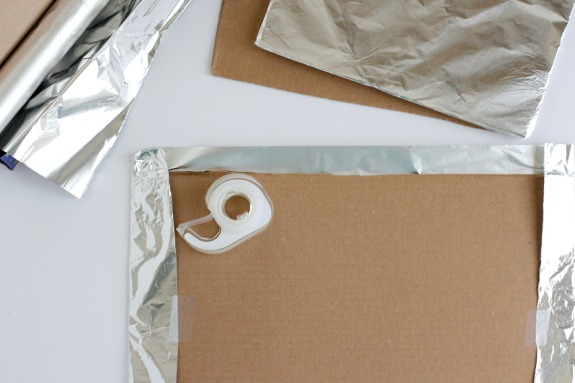 Wrapping tinfoil over cardboard to make candy houses