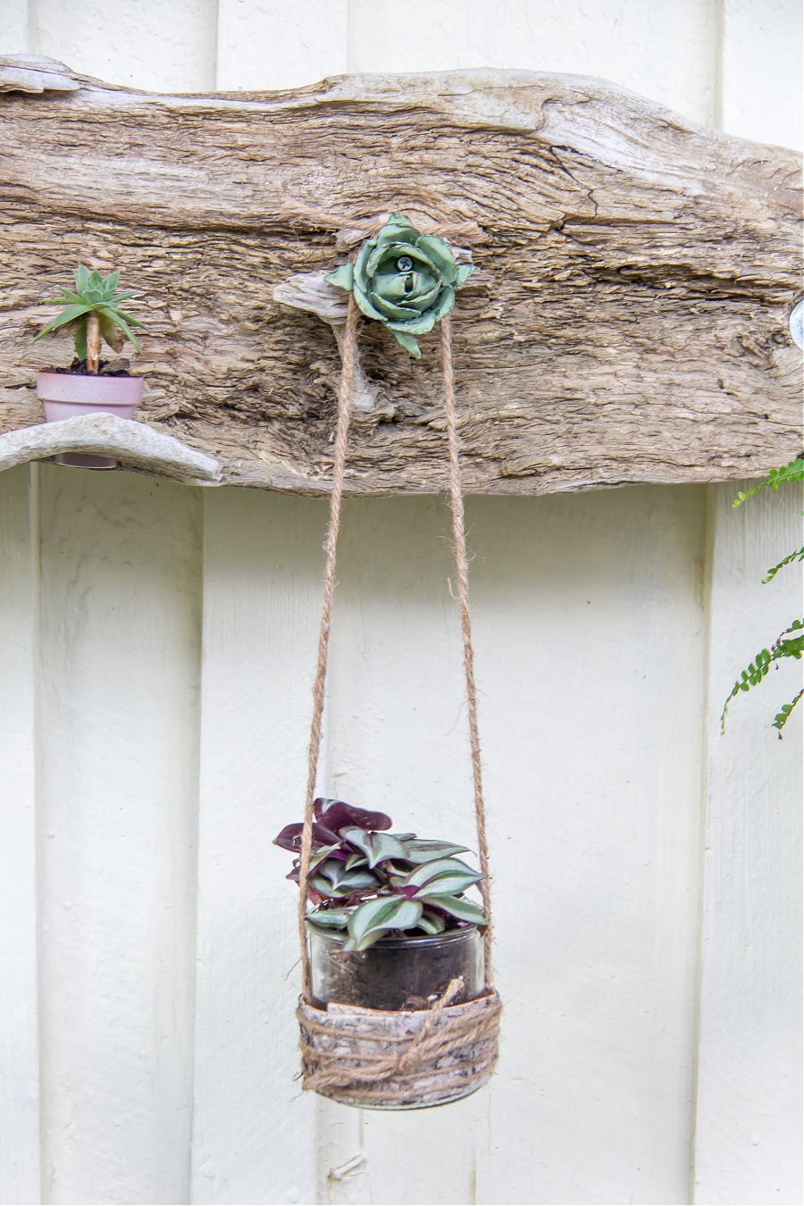 a green metal flower screwed to driftwood to hang a planter