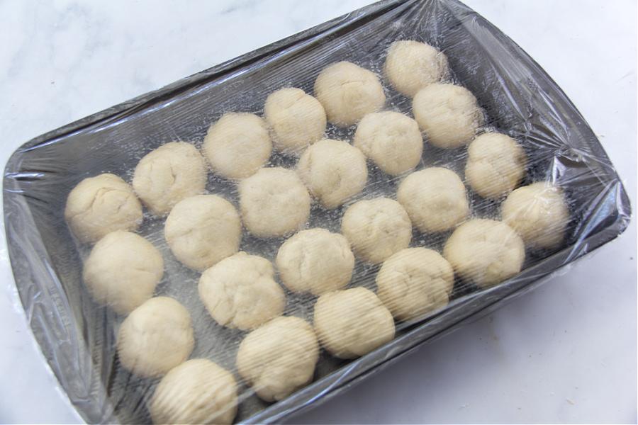 bread dough balls inside a baking dish to make dinner rolls