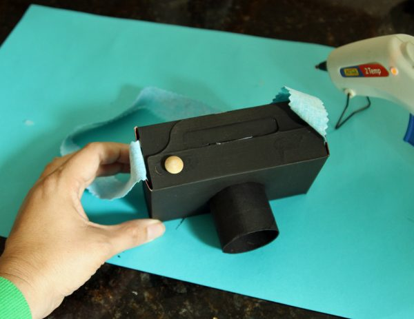 Cardboard play camera with strap and button
