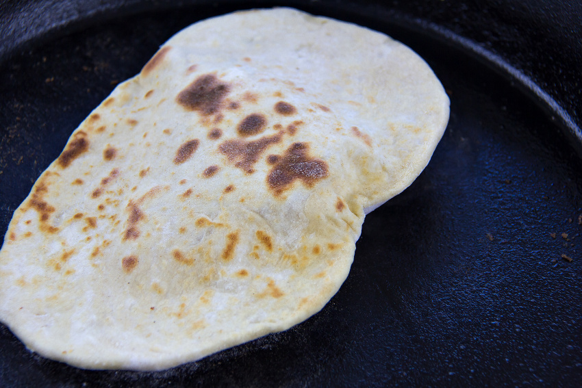 flatbread being cooked in a cast-iron skillet