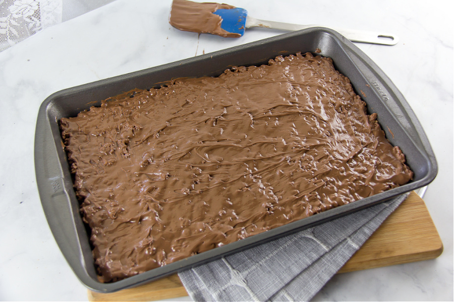 a baking pan with chocolate rice krispies coated in a layer of melted chocolate