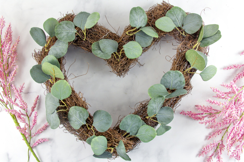a natural vine wreath with green leafy stems