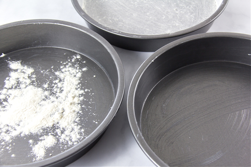three cake pans in stages of butter and flour for baking