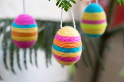 Brighten up your home this Easter with some adorable Hanging Yarn Wrapped Plastic Eggs. It's the perfect holiday craft to make with your kids!