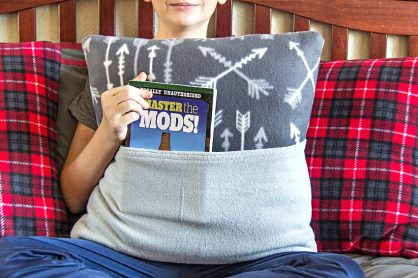a boy holding a grey fleece book pillow