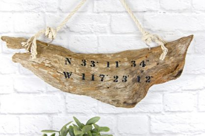 driftwood sign with co-ordinates stenciled onto it
