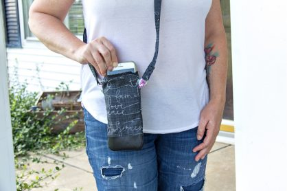a lady wearing a white t-shirt and jeans with a black cross-body phone purse