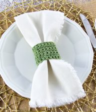 a holiday place setting in green, gold, and white