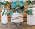 assorted vases wrapped in knit cozies and filled with winter flower arrangements