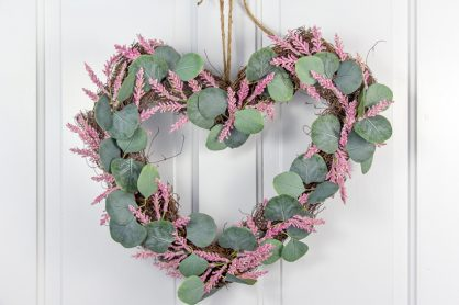 eucalyptus leaves and pink flowers on a natural heart shaped wreath