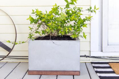 a handmade square concrete and wood planter