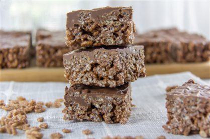 chocolate rice krispies treats stacked and a wood cutting board