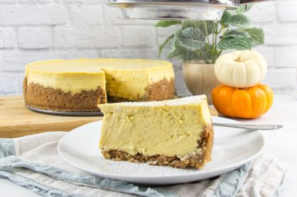 a slice of gluten free pumpkin cheese on a plate with the cheesecake on a board behind it