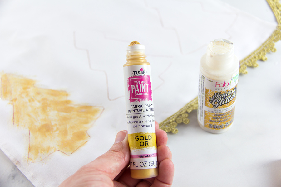 gold paint being used to paint gold christmas trees on a table runner