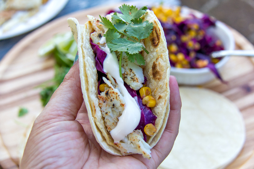 hand holding a fish taco with cabbage slaw