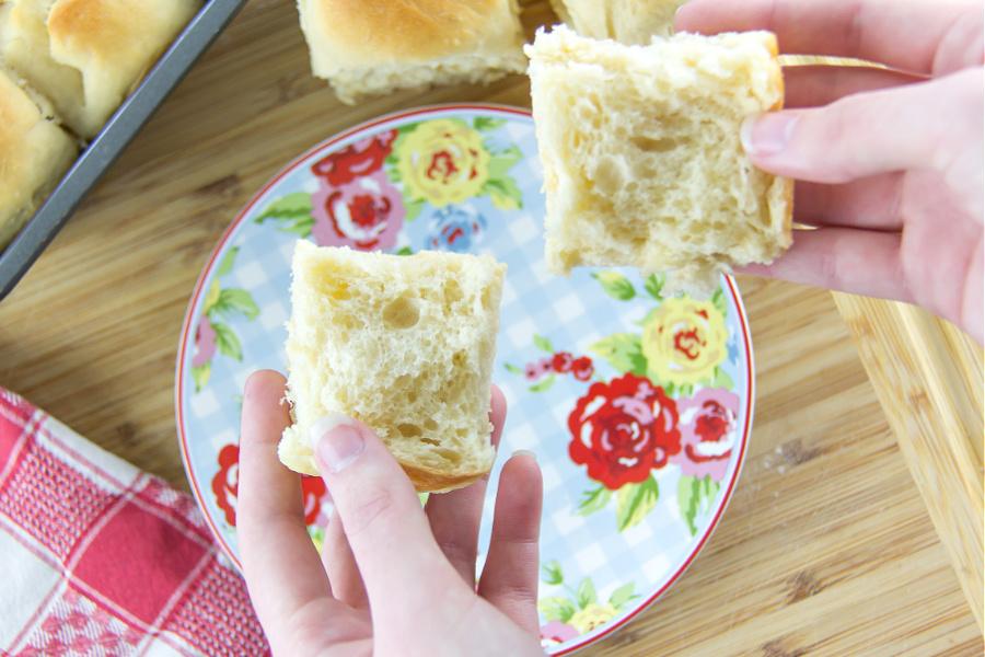 hands holding a homemade dinner roll broken in half