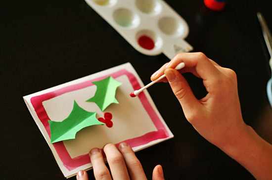 Painting holly berries on a Christmas card @makeandtakes.com