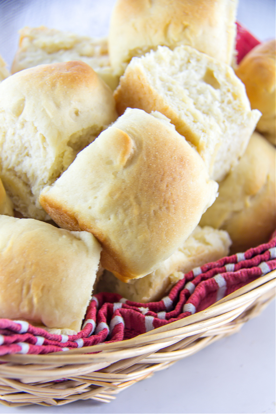 homemade yeast dinner rolls inside a basket with a red towel underneath