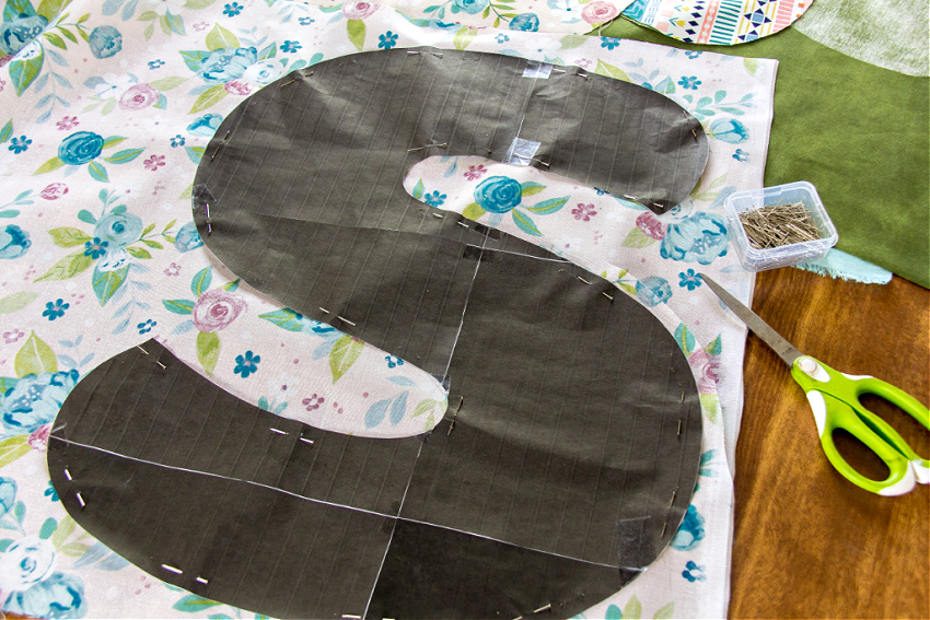 a large paper letter s pinned to fabric