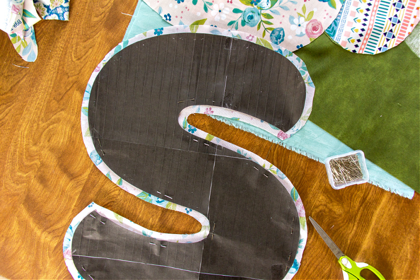 a letter s cut out of fabric using a paper template