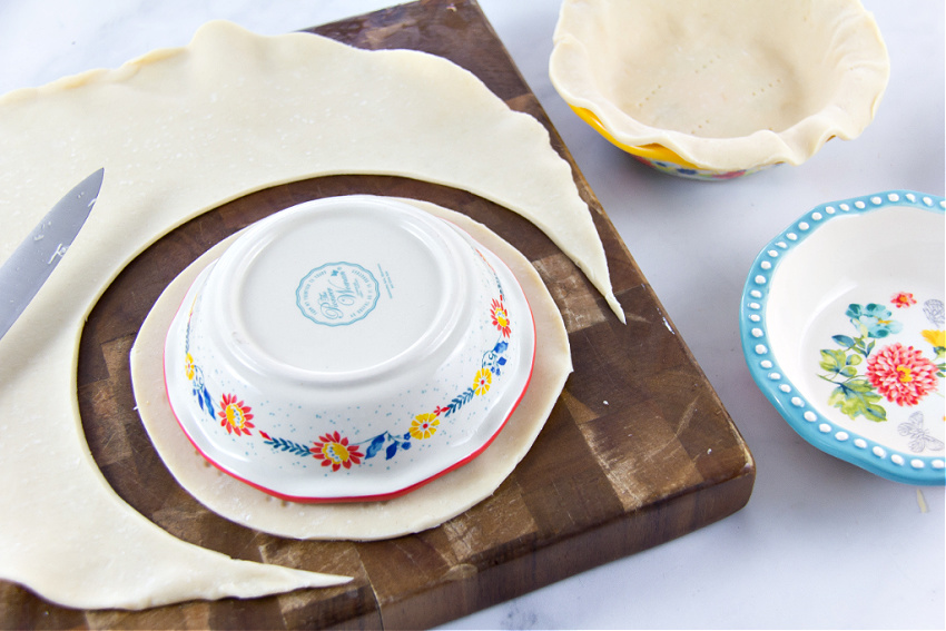 mini pie dishes on top of pie crust to measure size