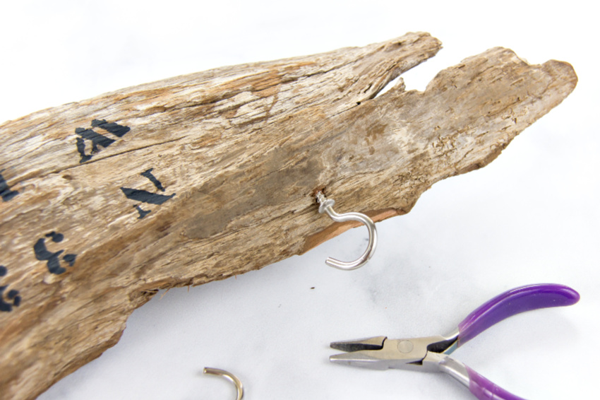 cup hooks being wound into a piece of driftwood