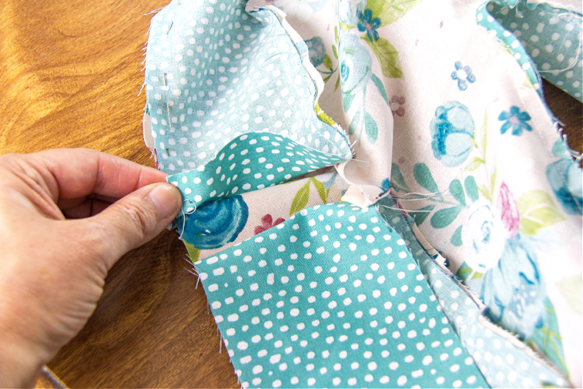 a hand holding fabric to be sewn