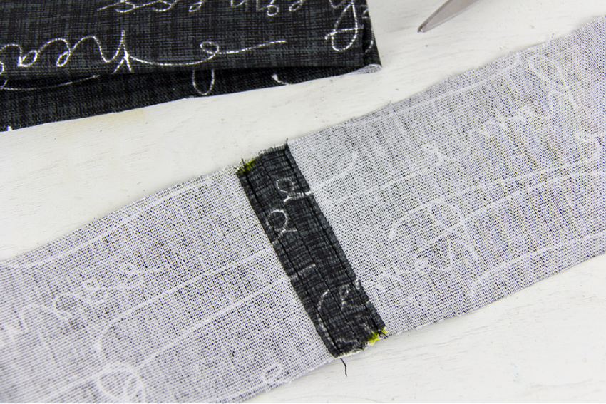fabric being sewn together to make a shoulder strap for a bag