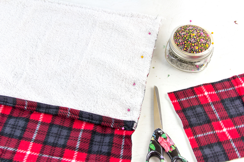 plaid fabric pinned to make a cushion cover