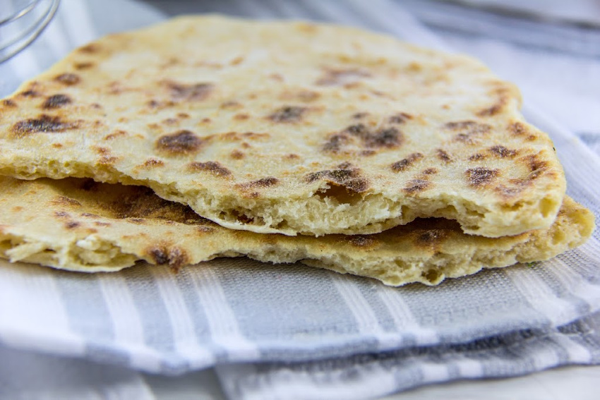 flatbread torn in half on a grey and white dishtowel