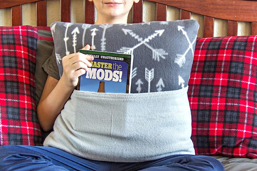 a boy holding a grey fleece book pillow
