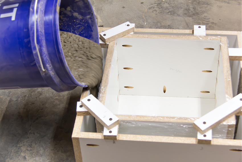 concrete being poured into a plywood box to make a planter