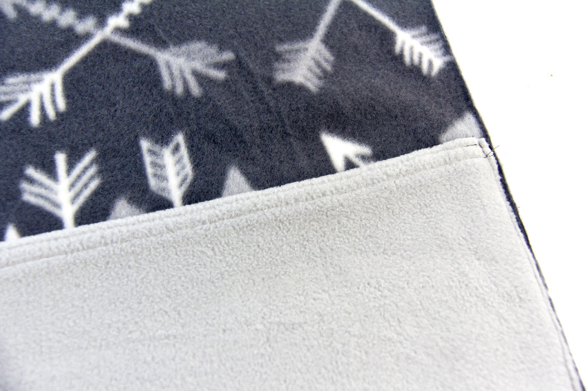 a grey pocket being sewn onto a dark grey pillow cover
