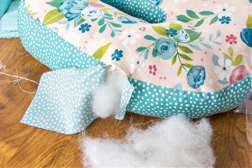 a handmade floral pillow being stuffed with polyfil
