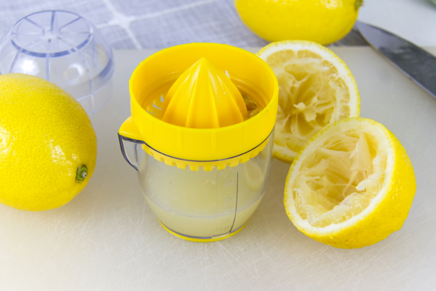 lemons being squeezed using a lemon juicer