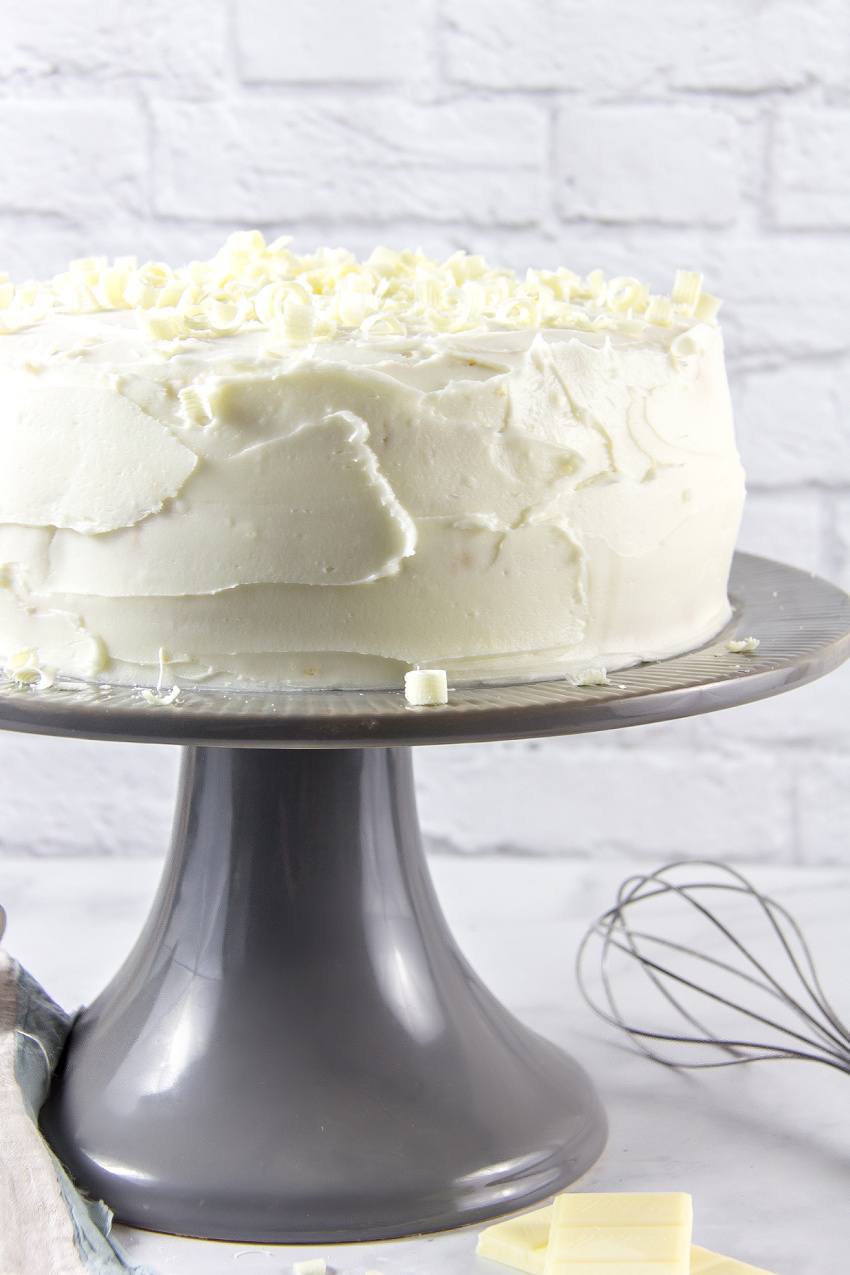 a white cake on a grey cake stand with baking tools
