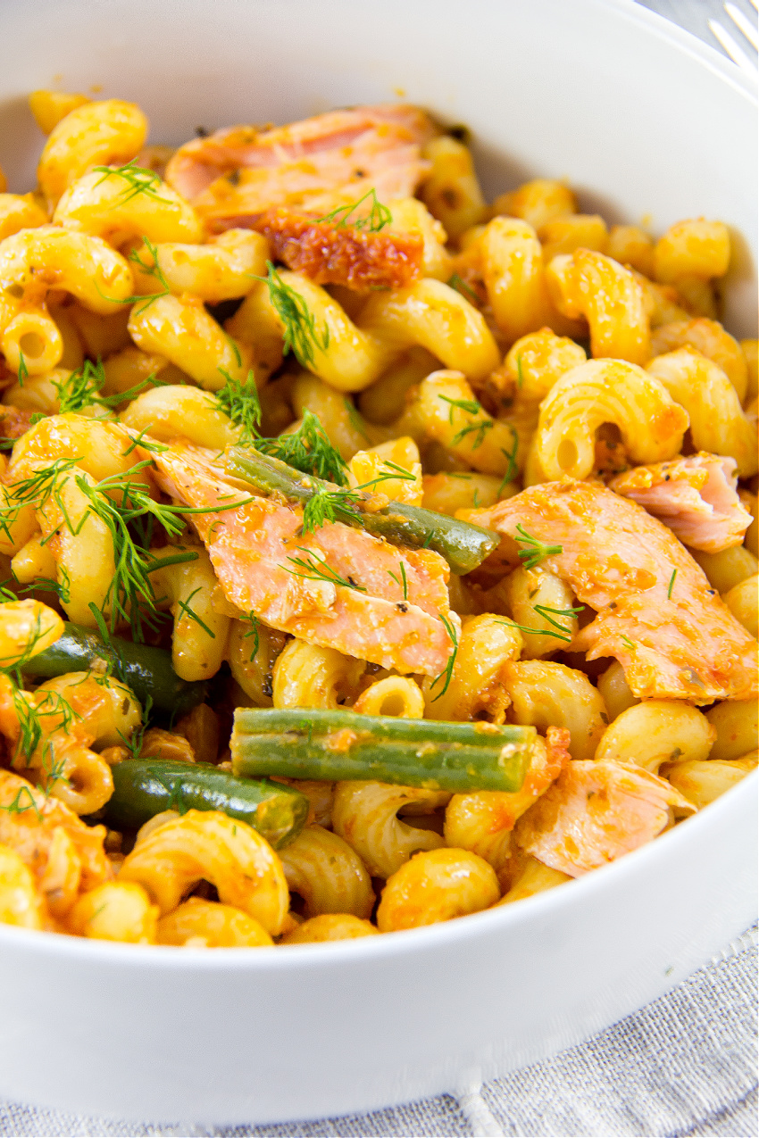 cellentani pasta with salmon and green beans in a white bowl