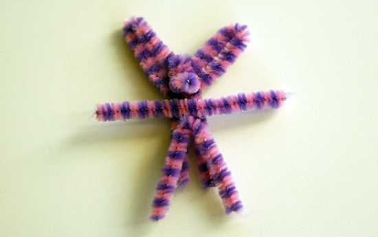 Attaching pipe cleaner arms and legs to bunny
