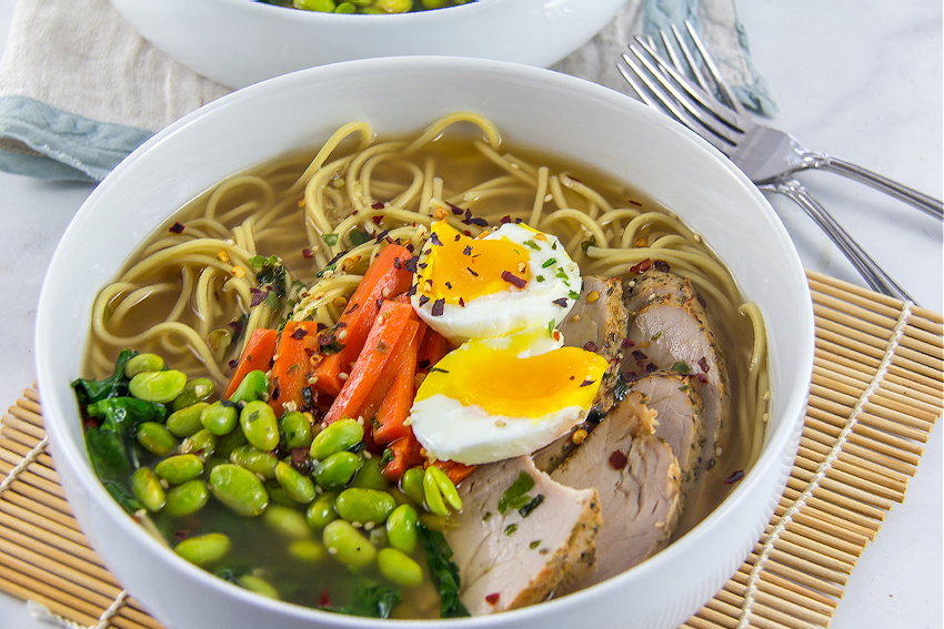 pork edamame and carrot with ramen noodles and egg in a bowl