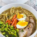 pork ramen in a white bowl topped with egg