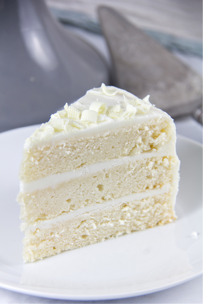 a slice of white cake with white frosting