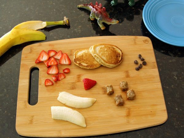 Making a stegosaurus with pancakes, sausage, and fruit