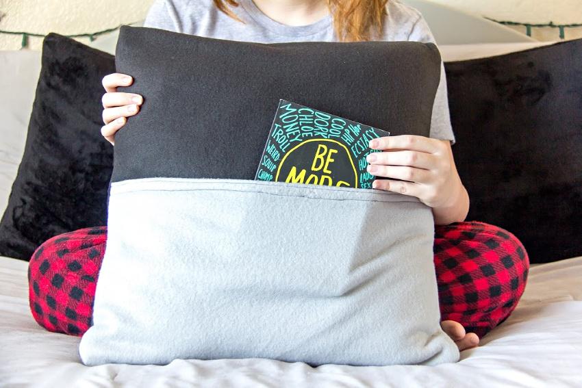 a teen girl holding a handmade book pillow